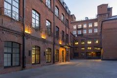 De mening van de nacht Moderne die zolder-Stijl bureaus in het oude fabrieksgebouw worden gevestigd Rode baksteenhuizen wijnoogst stock foto