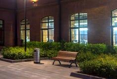De mening van de nacht Zaken - de Horizon van de Stad van Nietjes office gebouwen Lege bank en urn Rood baksteenhuis royalty-vrije stock foto