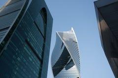 De mening van onderaan van eigentijdse lange wolkenkrabbers tegen blauwe hemel, gemeenschappelijke moderne bureaugebouwen in zake Stock Foto