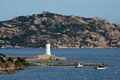 De mening van Palau vuurtoren met boten legde in het blauwe overzees van Sardinige vast stock foto