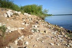 De mening van de rotsachtige bank van rivier met struik stock foto