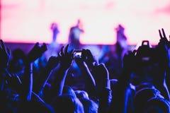 De mening van rotsoverleg toont in grote concertzaal, met menigte en de stadiumlichten, een overvolle concertzaal met scènelichte Stock Foto's