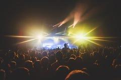 De mening van rotsoverleg toont in grote concertzaal, met menigte en de stadiumlichten, een overvolle concertzaal met scènelichte royalty-vrije stock foto's