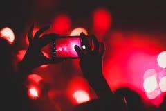 De mening van rotsoverleg toont in grote concertzaal, met menigte en de stadiumlichten, een overvolle concertzaal met scènelichte stock afbeeldingen