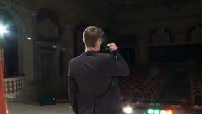 De mening van de rug, de kunstenaar komt uit achter de schermen op het stadium met een microfoon en begint te zingen stock footage