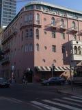 De mening van de straathoek van een kruispunt en een roze vier verhaalgebouw met geparkeerde auto's stock afbeelding
