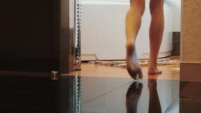 De mening van vrouw die aan badkamers lopen en gaat zitten op bad Sexy naakte benen stappen stock videobeelden