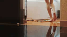 De mening van vrouw loopt elegant aan badkamers op tiptoe en gaat zitten op wit bad stock videobeelden