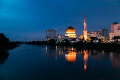 De mening van de Waterkant van de Klangstad tijdens blauw uur met bezinning in de rivier stock foto's
