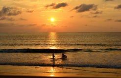 De mening van zonsondergangstrand heeft silhouetmensen speelt het overzees Royalty-vrije Stock Foto