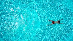 De mening vanaf de bovenkant als mens duikt in de pool en zwemt onder het water stock video