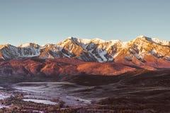 De meningen van de sneeuwpieken en de riviervallei bij dageraad stock afbeeldingen