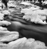 De menings bevroren beek van de nachtwinter, ijzige takjes en ijzige keien boven snelle stroom. Weerspiegelingen van licht in ijsk Royalty-vrije Stock Foto's