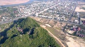 De menings groene heuvel van het vogeloog met tempeldaken onder moderne stad stock videobeelden