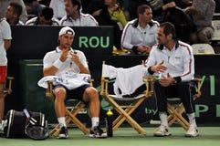 De mens Adrian die Ungur van het tennis tijdens een gelijke van de Kop van Davis rusten Stock Afbeeldingen