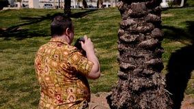 De mens in alohaoverhemd neemt foto's met retro camera in stadspark stock footage