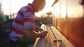 De mens is ambacht die bij een het werkbank met machtshulpmiddelen in slowmotion tijdens zonsondergang met mooie lensgloed werken stock video