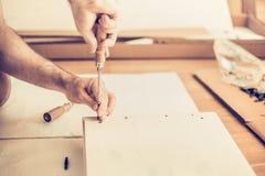 De mens assembleert garderobe, verdraait de schroeven de groeven, meubilairassemblage Stock Afbeelding