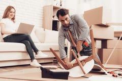 De mens assembleert uit Nieuwe het Meubilairdoos van Meubilairvouwen stock foto