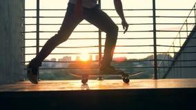De mens begint een skateboard op een stadsachtergrond, langzame motie te berijden stock videobeelden