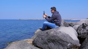 De mens begint om video op smartphone met driepoot te registreren zit op zee op reusachtige steen stock footage