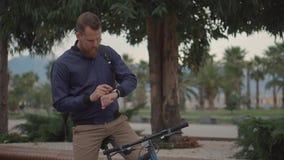 De mens bekijkt smartwatches op een rit stock footage