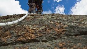 De mens beklimt omhoog bovenop de Rots stock videobeelden