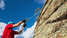 De mens beklimt omhoog bovenop de Rots stock footage