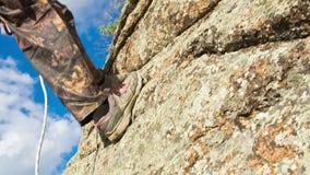 De mens beklimt omhoog bovenop de Rots stock video