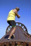 De mens beklimt tot de bovenkant van niet meer gebruikt maalmachinewiel Royalty-vrije Stock Afbeeldingen
