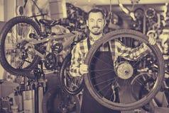 De mens bepaalt een fietswiel stock fotografie