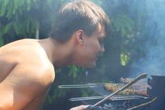 De mens bereidt een barbecue voor en geniet van de geur van voedsel Stock Fotografie