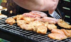 De mens bereidt kippenvlees en worsten bij de grill voor Royalty-vrije Stock Afbeeldingen