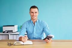 De mens berekent belasting bij bureau in bureau Stock Foto