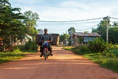 De mens berijdt een motor onderaan een landweg in Kambodja Stock Foto's
