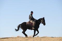 De mens berijdt het paard Stock Foto's