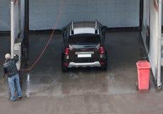 De mens betaalt voor het wassen van de auto in de autowasserettezelfbediening stock afbeelding