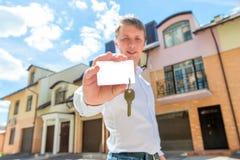 De mens bevindt zich dichtbij het huis en toont de sleutel Royalty-vrije Stock Fotografie