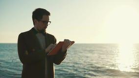 De mens bevindt zich dichtbij oceaan, houdend tablet in handen en wat betreft touchscreen stock footage