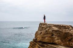 De mens bevindt zich op een overzeese klip, onderzoekend de afstand op een donkere stormachtige overzees Stock Fotografie