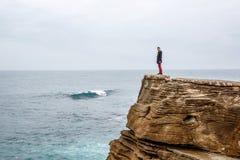De mens bevindt zich op een overzeese klip, onderzoekend de afstand op een donkere stormachtige overzees Royalty-vrije Stock Fotografie