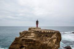 De mens bevindt zich op een overzeese klip, onderzoekend de afstand op een donkere stormachtige overzees Royalty-vrije Stock Afbeeldingen