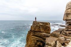 De mens bevindt zich op een overzeese klip, onderzoekend de afstand op een donkere stormachtige overzees Stock Foto's