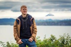 De mens bevindt zich op de kust van Avacha-Baai met vage vulkaan op de achtergrond royalty-vrije stock fotografie