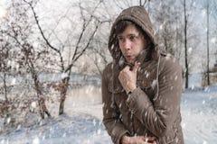 De mens bevriest buiten in de koude winter stock foto