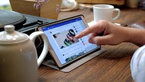 De mens bezoekt facebook website op tabletpc in een koffie stock video