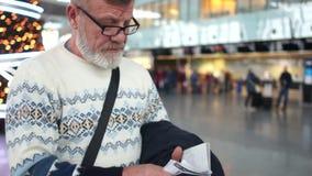 De mens bij de internationale luchthaven wacht op de aankomst van zijn vlucht Hij houdt een paspoort en een kaartje stock videobeelden