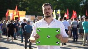 De mens bij toont met een aanplakbiljet aan Groene banner met punten voor het volgen 4k stock footage