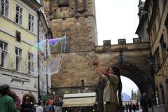 De mens blaast een reusachtige zeepbel op de straat Stock Foto's