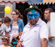 De mens in blauw masker bevindt zich en bekijkt arnival parade Ñ  Royalty-vrije Stock Afbeeldingen